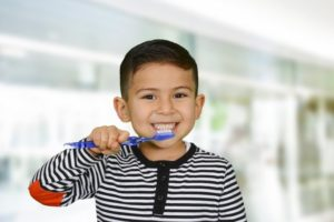 boy smiling while brushing his teeth