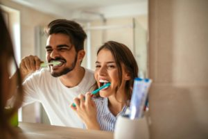 couple brushing their teeth in the mirror