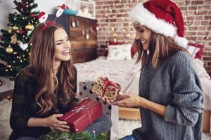 women exchanging holiday gifts