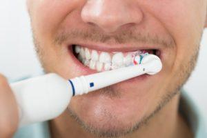 man using electric toothbrush