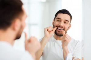 bearded man in white shirt flossing in front of mirror