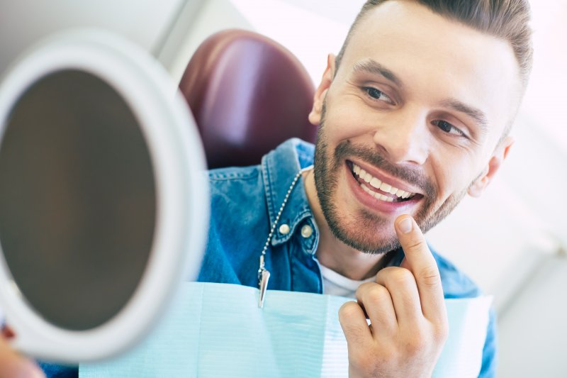 Patient with veneers smiling at reflection