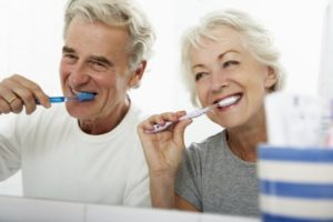 senior man and woman brushing their teeth together