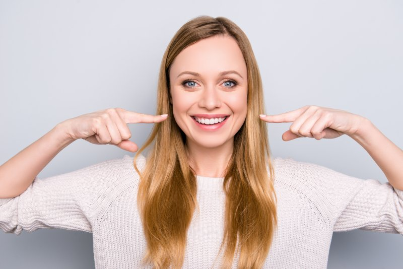 young woman pointing to her smile